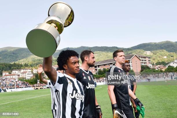 Juan Cuadrado of Juventus shows a trophy to the fans before the preseason friendly match between Juventus A and Juventus B on August 17 2017 in...