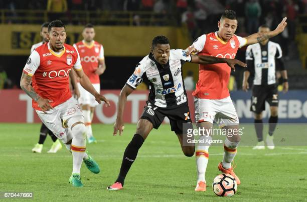 Juan Daniel Roa and Yeison Gordillo of Santa Fe struggle for the ball with Bruno Henrique of Santos during a group stage match between Independiente...