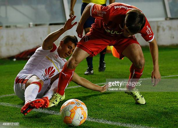 Juan Daniel Roa of Independiente Santa Fe slides for the ball as Nicolas Tagliafico of Independiente tries to dribble during a match between...