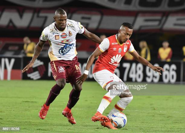 Juan David Valencia of Santa Fe fights for the ball with Erik Correa of Tolima during the semifinal match between Santa Fe and Deportes Tolima as...