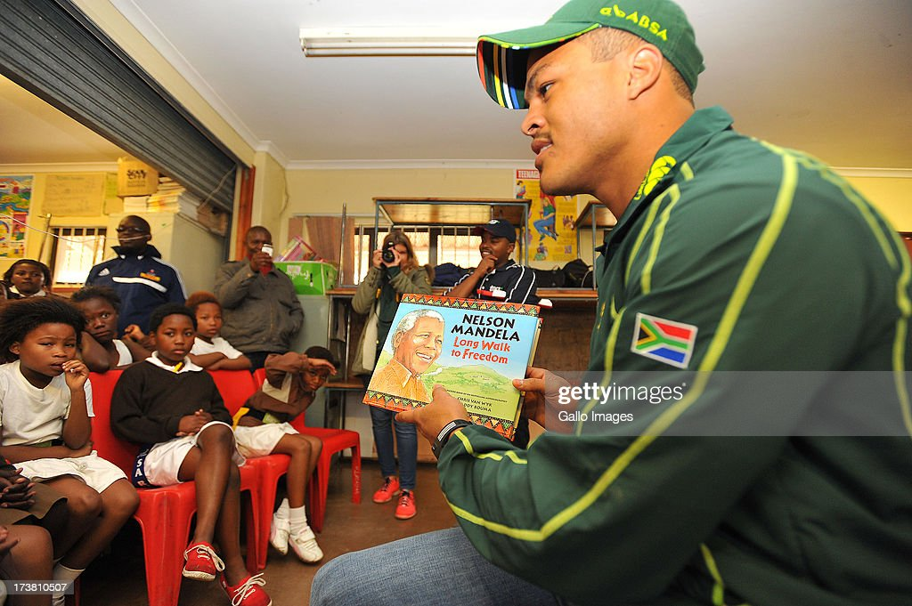 Juan de Jongh holding the book called, The Long walk to Freedom as he displays the cover to the kids during the SA Rugby's 67 minutes in honour of Nelson Mandela Day at Siyabulela Primary School on July 18, 2013 in Cape Town, South Africa.