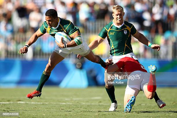 Juan de Jongh of South Africa is tackled by Phil Burgess of Great Britain the Men's Rugby Sevens semi final match between Great Britain and South...