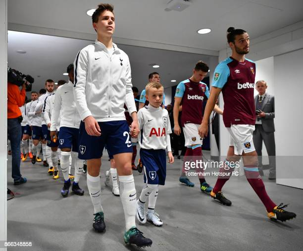Juan Foyth of Tottenham Hotspur and Andy Carroll of West Ham United lead their teams onto the pitch prior to the Carabao Cup Fourth Round match...