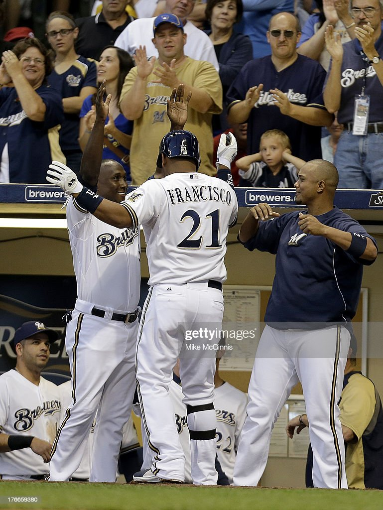 Juan Francisco of the Milwaukee Brewers celebrates with Yuniesky Betancourt and Martin Maldonado after hitting a solo home run in the bottom of the...