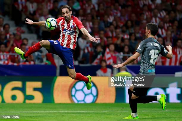 Juan Francisco Torres alias Juanfran of Atletico de Madrid competes for the ball with Federico Ricca of Malaga CF during the La Liga match between...