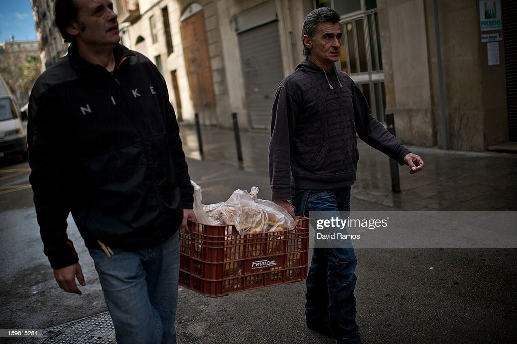 Juan from Spain and Walter from France carry pastries to 'El Chiringuito de Dios' ('The Stall of God') on January 4, 2013 in Barcelona, Spain. The German pastor Wolfgang Striebinger has lived in Barcelona since 1991, originally employed to minister to youths during the Barcelona Olympic Games, he decided to stay and since 2000 has run 'El Chinguito de Dios' (The Stall of God). In his mission to support the homeless, Wolfgang and his volunteers offer a place for up to 200 people to come and have some food daily and also offering them assistance with grooming and clothes. Many of the volunteers are homeless and help out in return for meals and a bed. Wolfgang's ethos is to provide peace, calm and dignity to all those that need it amongst Barcelona's burgeoning homeless population. Due to the economic situation his doors are now also open to the long term unemployed and families with little or no income. According to the latest figures 21.8% of the Spanish populations are living below the poverty line.