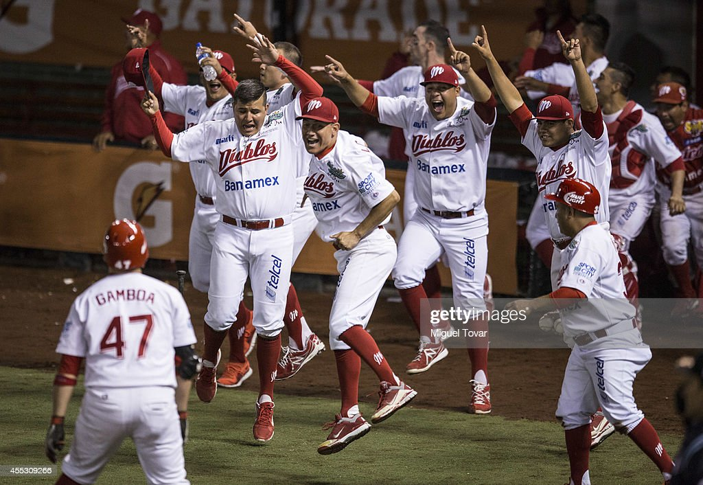 Juan Gamboa celebrates with teammates after making a home run to win the championship between Pericos de Puebla and Diablos Rojos as part of Serie...