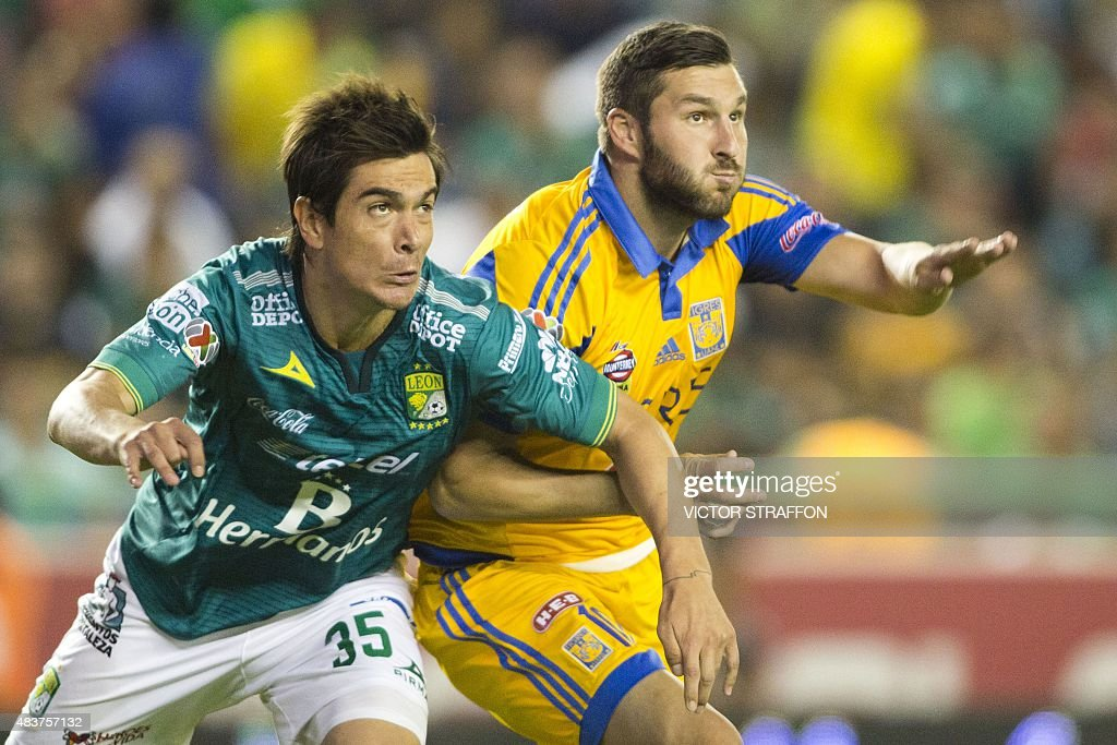 Juan Gonzalez of Leon vies for the ball with Andre Pierre Gignac of Tigres during their Mexican Apertura tournament football match at the Nou Camp...