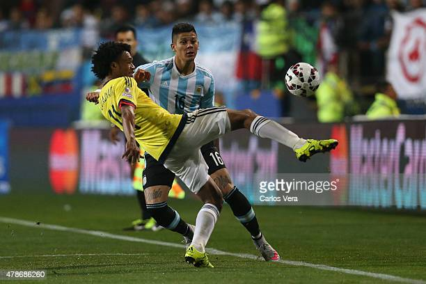 Juan Guillermo Cuadrado of Colombia fights for the ball with Marcos Rojo of Argentina during the 2015 Copa America Chile quarter final match between...