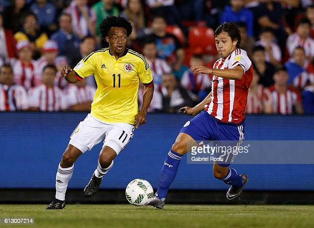 Juan Guillermo Cuadrado of Colombia fights for the ball with Oscar Romero of Paraguay during a match between Paraguay and Colombia as part of FIFA...