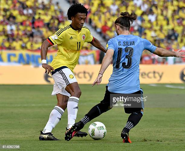 Juan Guillermo Cuadrado of Colombia vies for the ball with Gaston Silva of Uruguay during a match between Colombia and Uruguay as part of FIFA 2018...