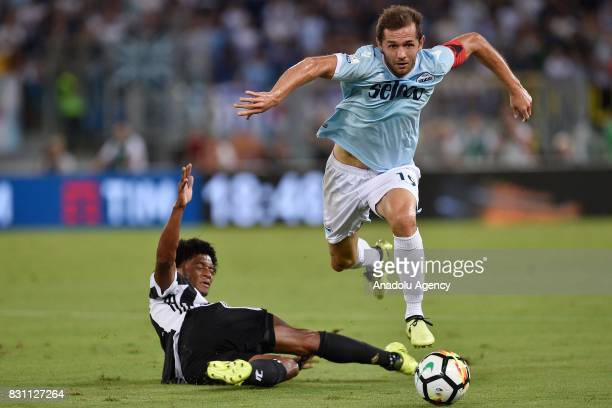 Juan Guillermo Cuadrado of FC Juventus in action against Senad Lulic of SS Lazio during the Italian Super Cup soccer match between FC Juventus and SS...