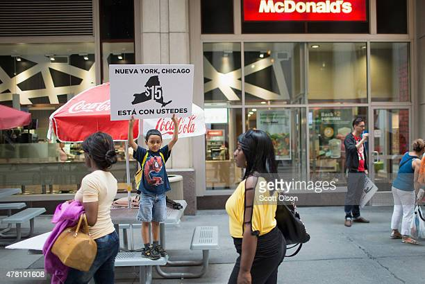 Juan Hernandez protests with his mother who works for McDonald's and other fast food workers and community activists outside a McDonald's restaurant...