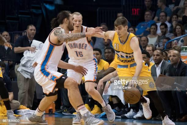 Juan Hernangomez of the Denver Nuggets tries to drive around Steven Adams of the Oklahoma City Thunder and Kyle Singler of the Oklahoma City Thunder...