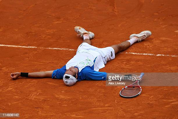 Juan Ignacio Chela of Argentina falls to the court as he celebrates matchpoint during the men's singles round four match between Alejandro Falla of...