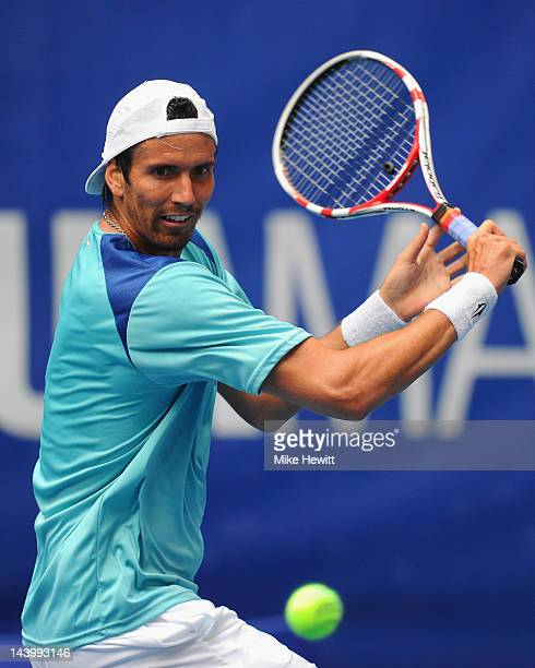 Juan Ignacio Chela of Argentina plays a backhand during his defeat to qualifier Alejandro Falla of Colombia in the Mutua Madrilena Madrid Open at the...