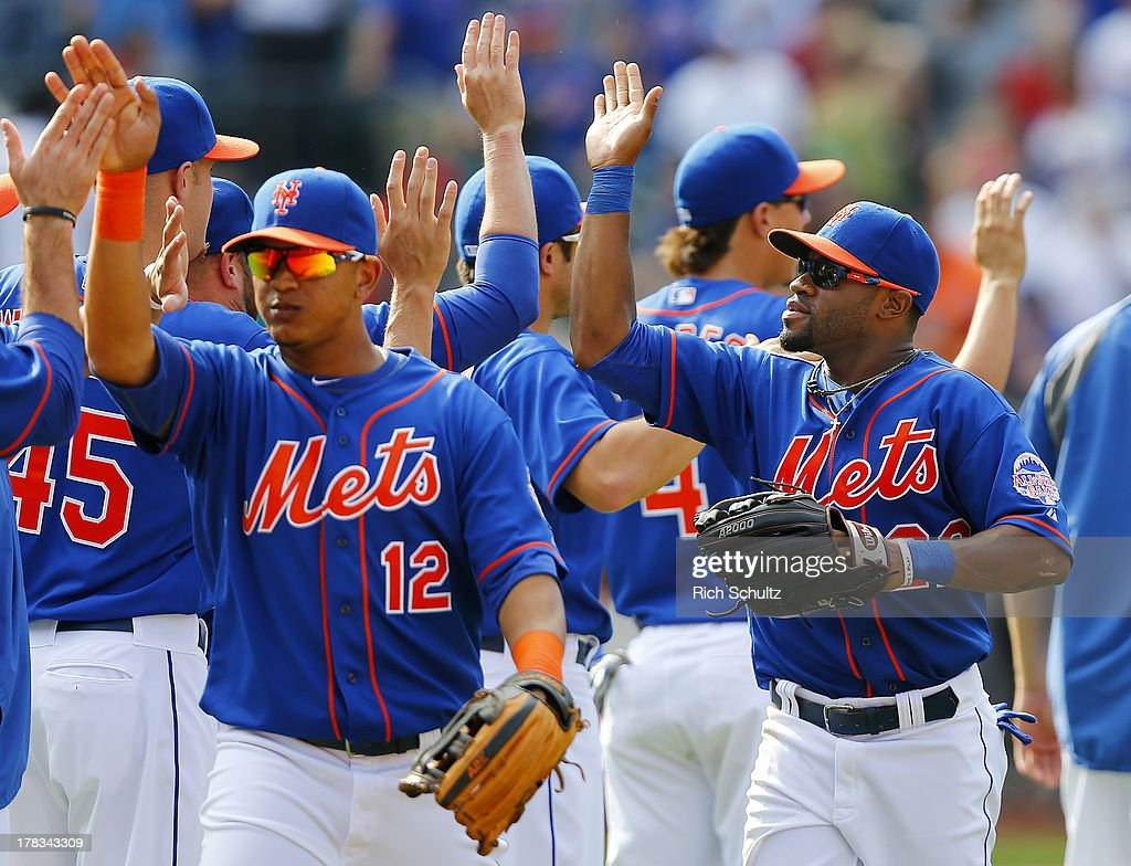 Juan Lagares #12 and Eric Young #22 of the New York Mets are congratulated by teammates after defeating the Philadelphia Phillies 11-3 on August 29, 2013 at Citi Field in the Flushing neighborhood of the Queens borough of New York City.