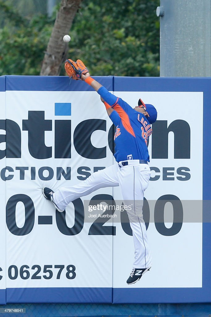Juan Lagares #12 of the New York Mets catches the ball hit by Justin Upton #8 of the Atlanta Braves in the first inning during a spring training game at Tradition Field on March 20, 2014 in Port St. Lucie, Florida.