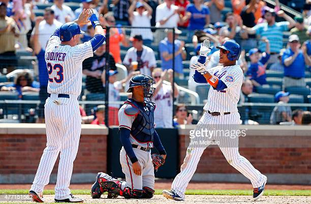 Juan Lagares of the New York Mets celebrates his sixth inning three run home run with teammate Michael Cuddyer as Christian Bethancourt of the...
