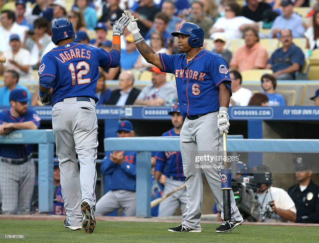 Juan Lagares #12 of the New York Mets is greeted by Marlon Byrd #6 as he returns to the dugout after hitting a solo home run against the Los Angeles Dodgers in the first inning at Dodger Stadium on August 13, 2013 in Los Angeles, California.