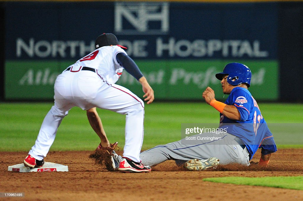 Juan Lagares #12 of the New York Mets is tagged out at second base on a pickoff play by <a gi-track='captionPersonalityLinkClicked' href=/galleries/search?phrase=Andrelton+Simmons&family=editorial&specificpeople=8978424 ng-click='$event.stopPropagation()'>Andrelton Simmons</a> #19 of the Atlanta Braves at Turner Field on June 20, 2013 in Atlanta, Georgia.