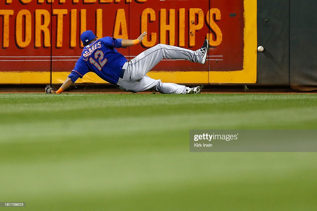 Juan Lagares #12 of the New York Mets loses his footing while chasing after the ball during the game against the Cincinnati Reds at Great American Ball Park on September 23, 2013 in Cincinnati, Ohio. Cincinnati defeated New York 3-2 in 10 innings.