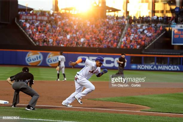Juan Lagares of the New York Mets scores from third base in the first inning on a fly ball from Yoenis Cespedes of the New York Mets as the sun goes...