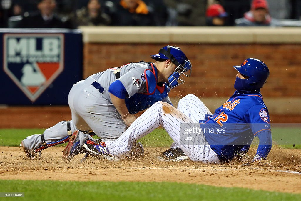 Juan Lagares of the New York Mets slides safe to home plate against Miguel Montero of the Chicago Cubs to score a run off of Curtis Granderson's...