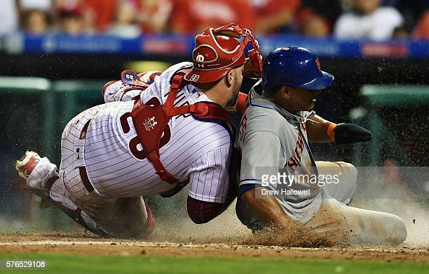 Juan Lagares of the New York Mets slips under the tag of Cameron Rupp of the Philadelphia Phillies in the seventh inning at Citizens Bank Park on...
