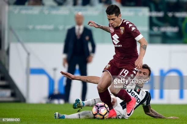 Juan Manuel Iturbe of Torino FC competes with Mario Mandzukic of Juventus FC during the Serie A football match between Juventus FC and Torino FC...