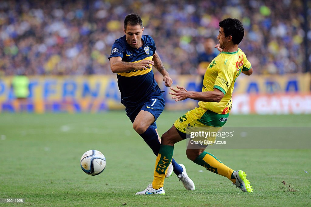 Juan Manuel Martinez of Boca Juniors struggles for the ball with Axel Juárez of Defensa y Justicia during a match as part of round 5 of Torneo Primera Division 2015 at Alberto J. Armando Stadium on March 14, 2015 in Buenos Aires, Argentina.