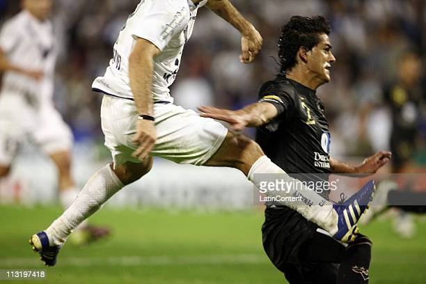 Juan Manuel MArtinez of Velez Sarsfield struggles for the ball with Norberto Araujo of Union LDU Quito during a match as part of Copa Libertadores de...