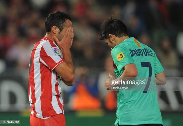 Juan Manuel Ortiz of UD Almeria reacts beside David Villa of Barcelona after Barcelona scored their fifth goal during the La Liga match between UD...