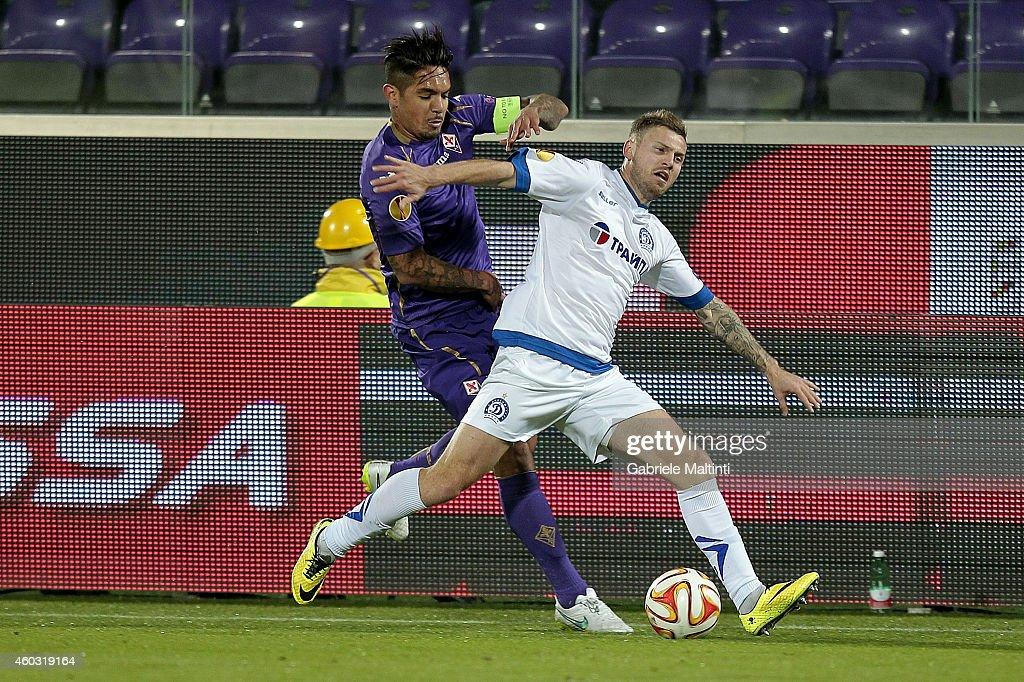 Juan Manuel Vargas of ACF Fiorentina fights for the ball with Oleg Veretilo of FC Dinamo Minsk during the UEFA Europa League group K match between ACF Fiorentina and FC Dinamo Minsk on December 11, 2014 in Florence, Italy.