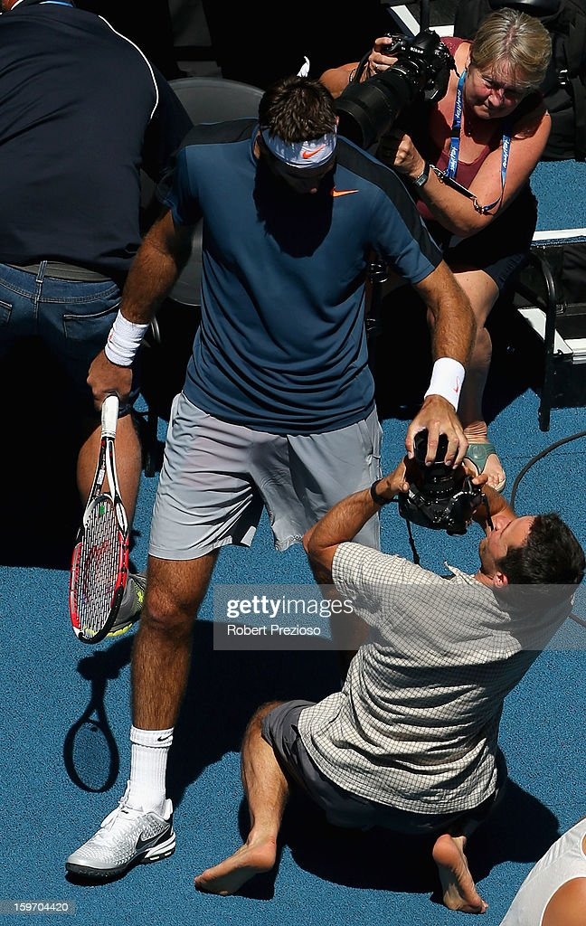 Juan Martin Del Potro of Argentina fends away a photographer after jumping into the photographers area after a point in his third round match against Jeremy Chardy of France during day six of the 2013 Australian Open at Melbourne Park on January 19, 2013 in Melbourne, Australia.