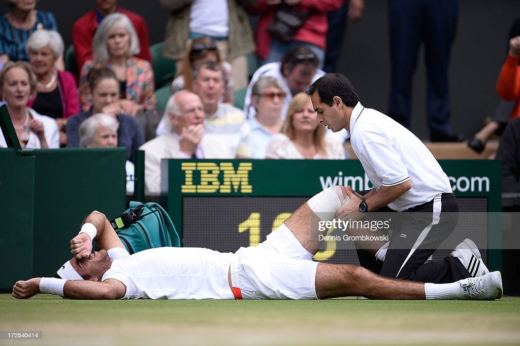Juan Martin Del Potro of Argentina grimaces as he receives treatment after slipping on the grass during the Gentlemen's Singles quarter-final match against David Ferrer of Spain on day nine of the Wimbledon Lawn Tennis Championships at the All England Lawn Tennis and Croquet Club at Wimbledon on July 3, 2013 in London, England.