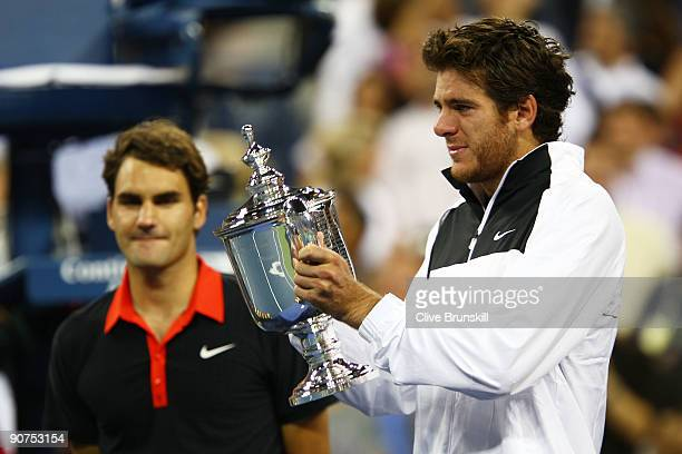 Juan Martin Del Potro of Argentina holds the championship trophy as Roger Federer of Switzerland looks on in the Men's Singles final on day fifteen...