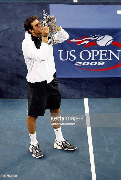 Juan Martin Del Potro of Argentina kisses the championship trophy after defeating Roger Federer of Switzerland in the Men's Singles final on day...