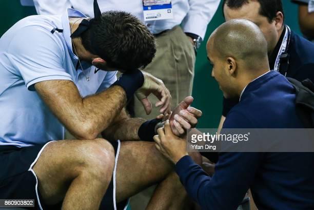 Juan Martin del Potro of Argentina receives medical treatment for his injured wrist during the Men's singles quarter final mach against Viktor...