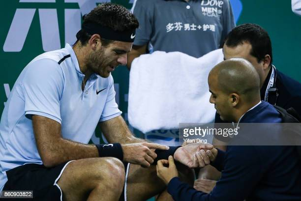 Juan Martin del Potro of Argentina receives medical treatment for his injured wrist during the Men's singles quarter final mach against Viktor...
