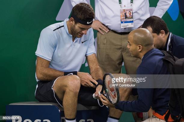 Juan Martin Del Potro of Argentina receives treatment after he fell during his men's singles quarterfinal match against Viktor Troicki of Serbia at...