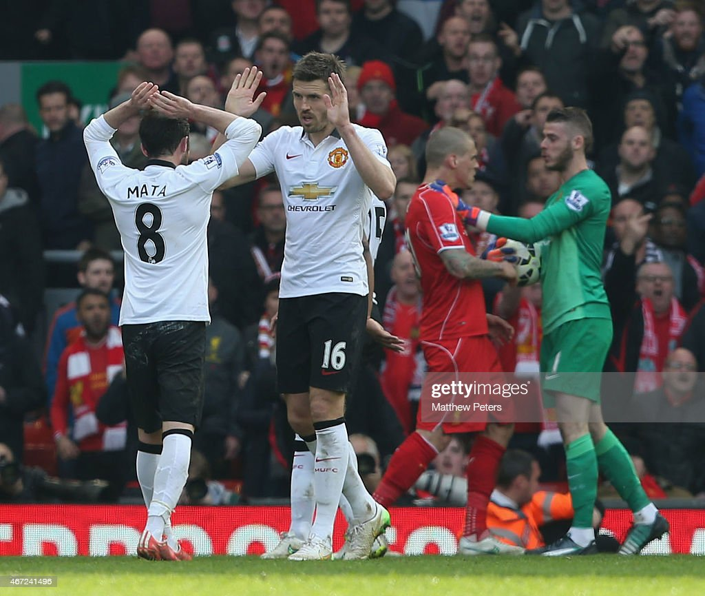 Juan Mata and Michael Carrick of Manchester United celebrate as David de Gea and Martin Skrtel of Liverpool clash after the Barclays Premier League match between Liverpool and Manchester United at Anfield on March 22, 2015 in Liverpool, England.
