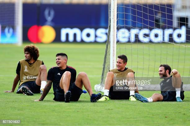 Juan Mata Ander Herrera and Marcos Rojo look on during a Manchester United training session ahead of the UEFA Super Cup at the National Arena Filip...