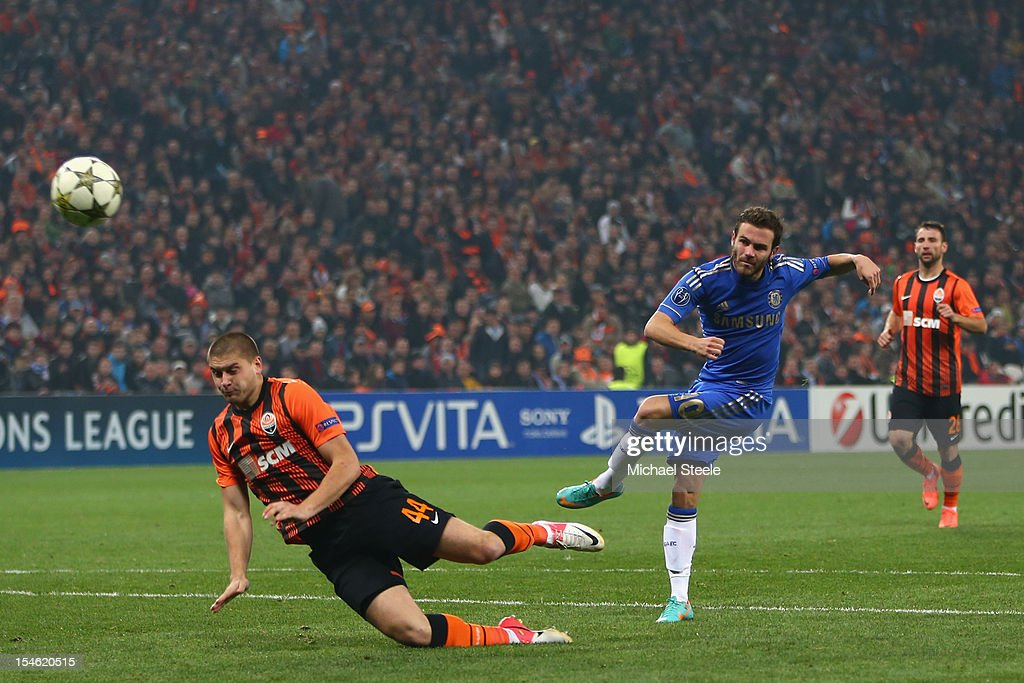 Juan Mata (R) of Chelsea shoots as Yaroslav Rakitskiy (L) of Shakhtar Donetsk attempts a block during the UEFA Champions League Group E match between Shakhtar Donetsk and Chelsea at the Donbass Arena on October 23, 2012 in Donetsk, Ukraine.