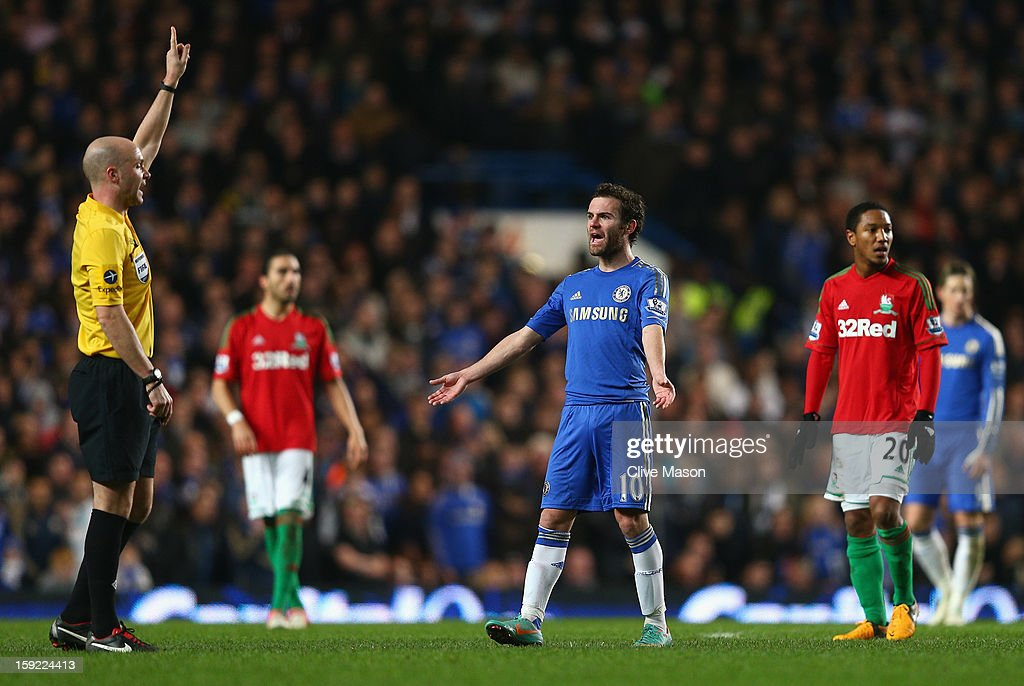 Juan Mata of Chelsea talks to referee Anthony Taylor during the Capital One Cup Semi-Final first leg match between Chelsea and Swansea City at Stamford Bridge on January 9, 2013 in London, England.