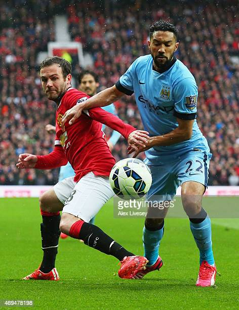 Juan Mata of Manchester United and Gael Clichy of Manchester City battle for the ball during the Barclays Premier League match between Manchester...