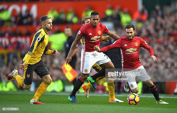 Juan Mata of Manchester United attempts to take the ball past Aaron Ramsey of Arsenal during the Premier League match between Manchester United and...