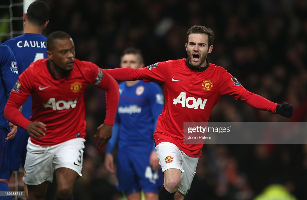 Juan Mata of Manchester United celebrates Robin van Persie scoring their first goal during the Barclays Premier League match between Manchester...