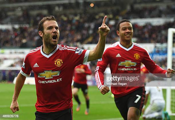 Juan Mata of Manchester United celebrates scoring the opening goal with Memphis Depay during the Barclays Premier League match between Swansea City...