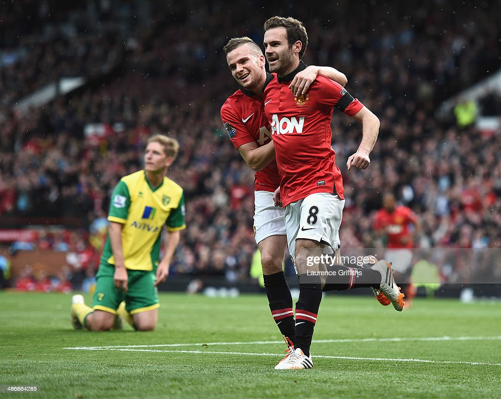 Juan Mata of Manchester United celebrates scoring the third goal with Tom Cleverley during the Barclays Premier League match between Manchester United and Norwich City at Old Trafford on April 26, 2014 in Manchester, England.